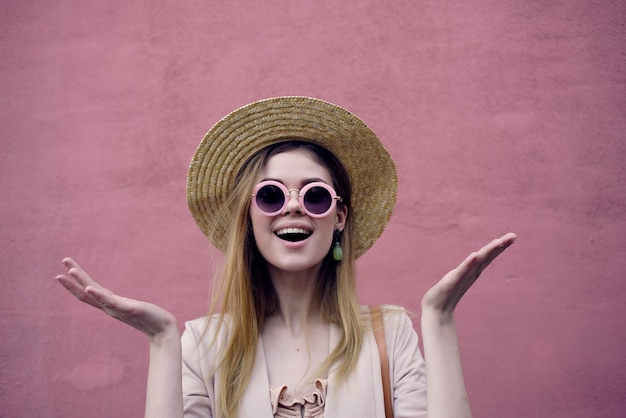 帽子とメガネのピンクの壁のモデルを身に着けている通りの女性