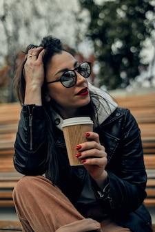 Женщина на улице с одноразовым бумажным стаканчиком. уберите еду, погуляйте по городу.