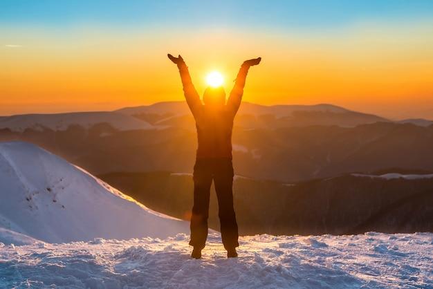 彼女の手で太陽を保持している冬の山の頂上に女性