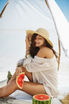 Женщина на тропическом пляже ест арбуз