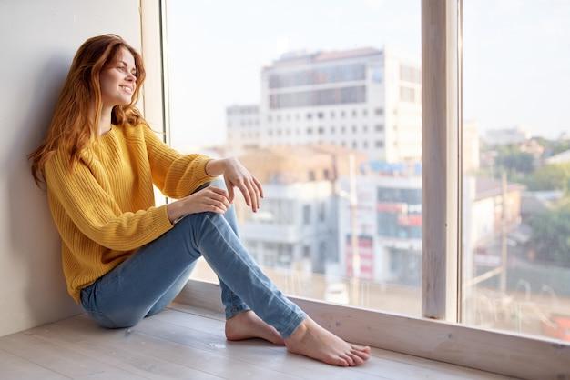黄色いセーターとジーンズのレジャーライフスタイルの窓辺の女性