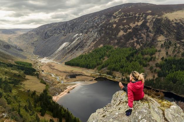Женщина на вершине горы в глендалох в ирландии