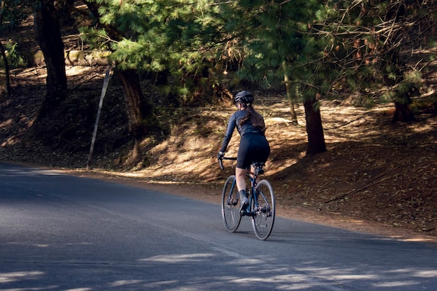 Женщина на велосипеде по тропе на дороге посреди концепции спорта на открытом воздухе в лесу