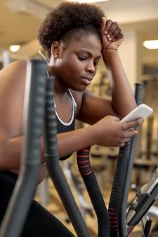Женщина на беговой дорожке с помощью мобильного телефона