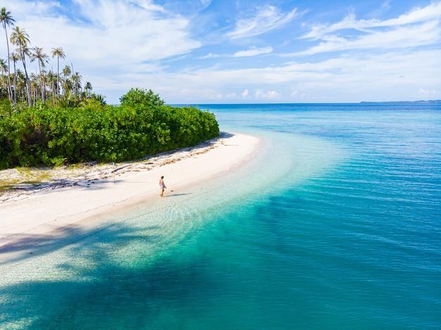 Женщина на тропическом пляже на островах тайлана баньяк, тропический архипелаг суматра, индонезия, ачех, коралловый риф с белым песком