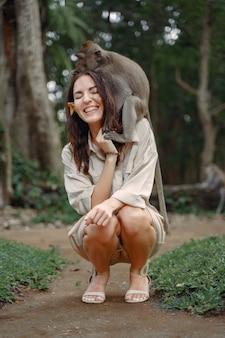 猿と遊ぶ休暇の女性