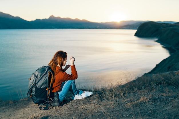 일몰 바다 근처 산에서 쉬고 휴가에 여자. 고품질 사진