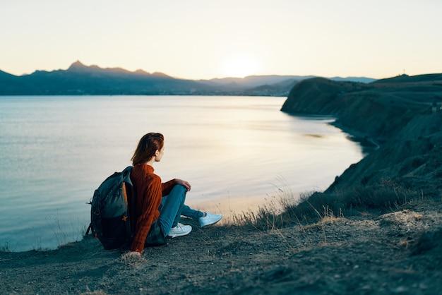 일몰 바다 근처 산에서 쉬고 휴가에 여자