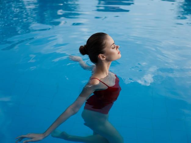 プールで泳いで休暇中の女性透明な水赤い水着リラックスモデル