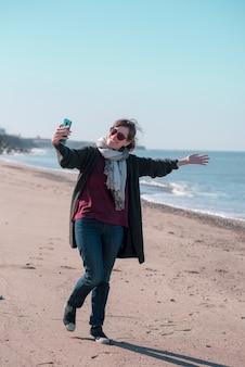 해변에서 셀카를 찍는 휴가 중인 여성