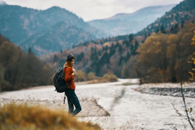 山の川岸にバックパックを持って休暇中の女性