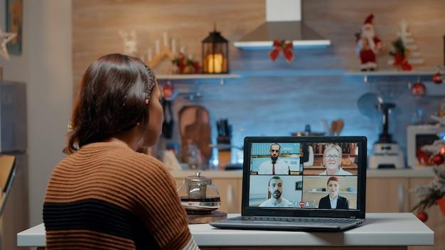 自宅で同僚とビデオ通話中の女性