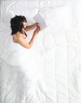 Женщина на белой кровати читает книгу