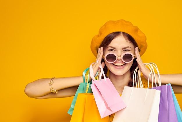 Женщина на желтом фоне улыбается с хозяйственными сумками в руках
