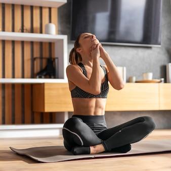 Женщина на коврике для йоги полный выстрел