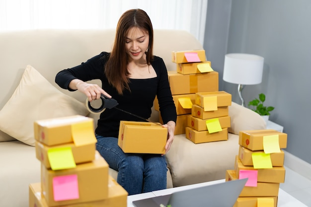 Woman online entrepreneur using tape to packing parcel box at home office, prepare product for deliver to customer