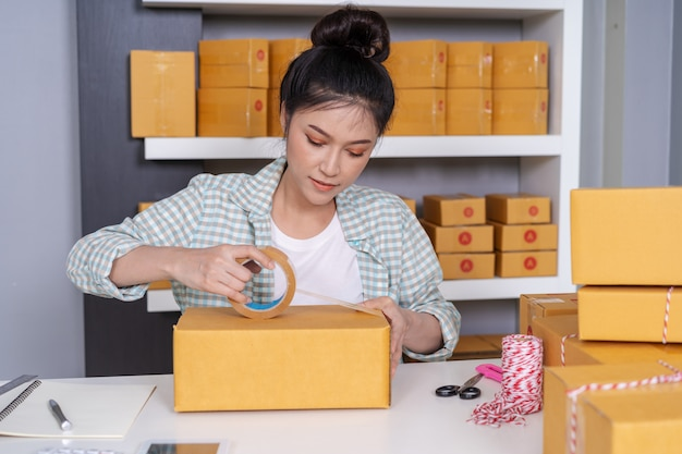 Woman online entrepreneur using tape to packing parcel box at home office