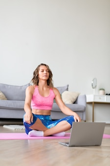 Woman in online yoga lesson
