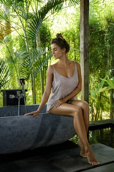 Woman in open air bathroom with stone bath in balinese style