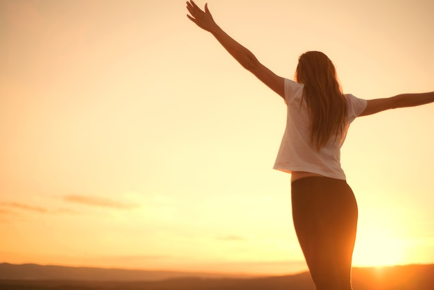 Woman open arms under the sunset. concept of healthy life.