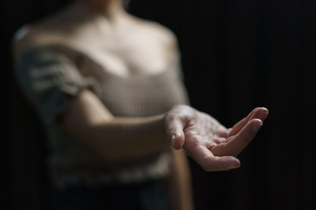女性は黒い背景に空の手を開きます。