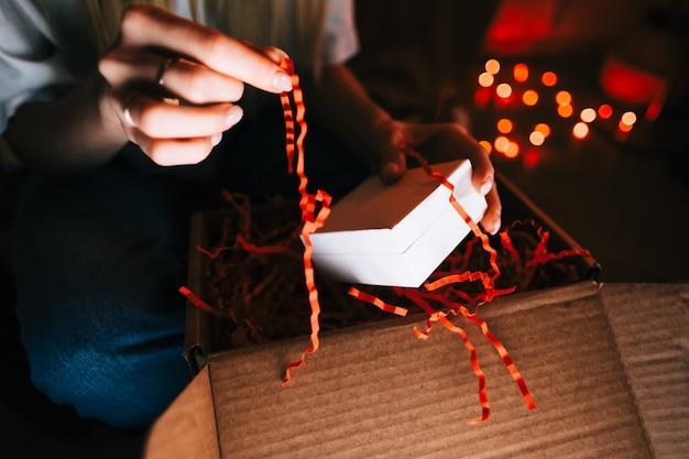 Женщина открывает подарок во время видеозвонка на портативном компьютере и пьет вино, использует технологии для общения с друзьями или семьей.