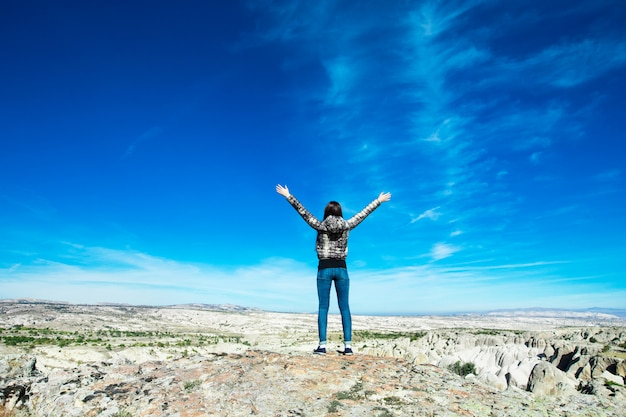 Woman open her arms in the mountain