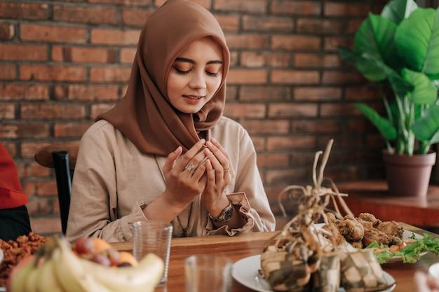 女性は彼女の手のひらを開き、食べる前に祈る
