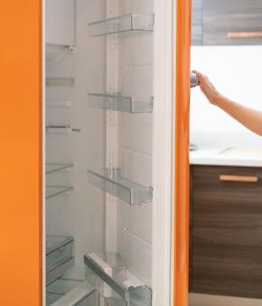 Женщина открыла дверь холодильника на кухне