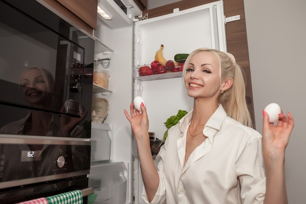 Woman at an open refrigerator with chicken eggs in hands