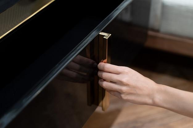 女性は棚を開け、黒いキャビネットに開いた引き出しを引き込みます。