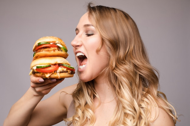 The woman opened her mouth to eat a hamburger