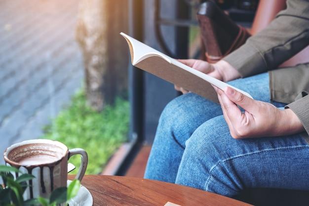 카페에서 나무 테이블에 노트북과 커피 컵으로 읽을 책을 여는 여자