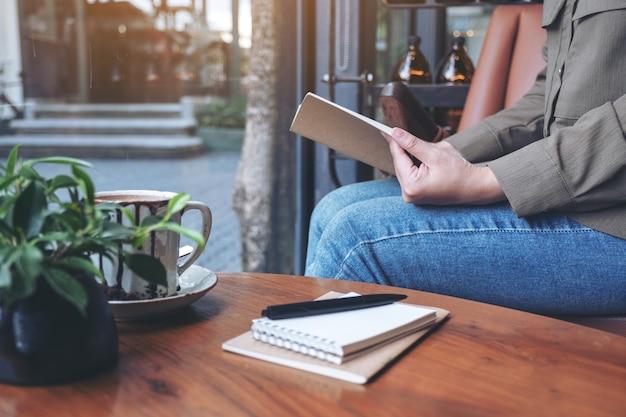 카페에서 나무 테이블에 노트북과 커피 컵과 책을 여는 여자
