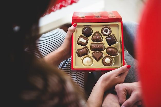 チョコレートの箱を開ける女