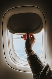 窓の陰を開く女性