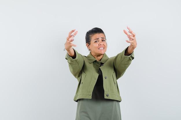 Женщина открывает руки для объятий в куртке, футболке и выглядит взволнованной.