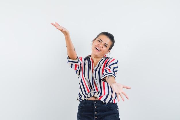Женщина раскрывает объятия в рубашке, юбке и выглядит веселой.