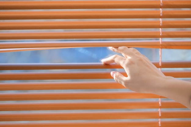 Woman opening blinds on window