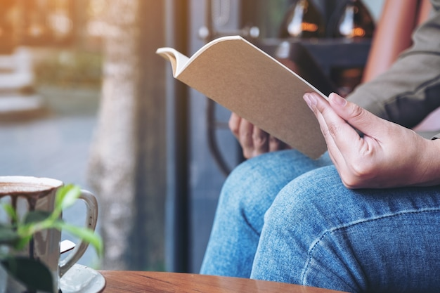 Woman opening a book to read with notebooks and coffee cup on wooden table in cafe
