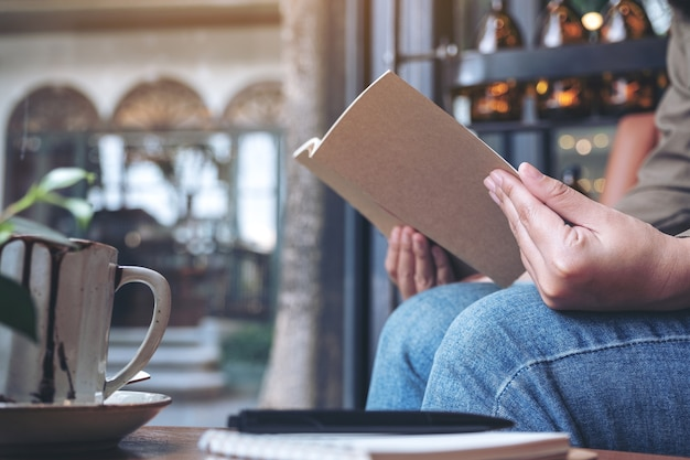 Woman opening a book with notebooks and coffee cup on wooden table in cafe