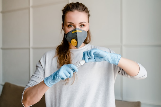 Woman opening bottle with hand sanitizer wearing mask and gloves at home
