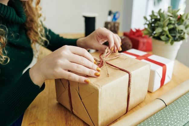 女性のクリスマスプレゼントを開く