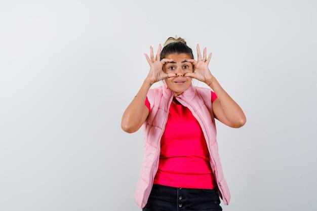 Женщина открывает глаза руками в футболке, жилете и выглядит мило