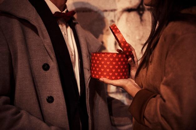Женщина открывает подарочную коробку мужчине