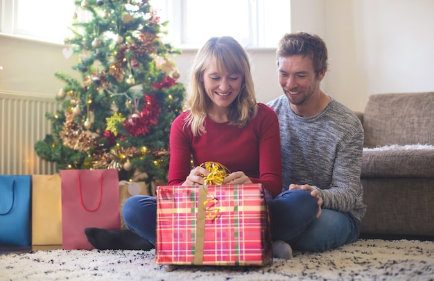 Woman opening her christmas gift while her boyfriend is hugging her