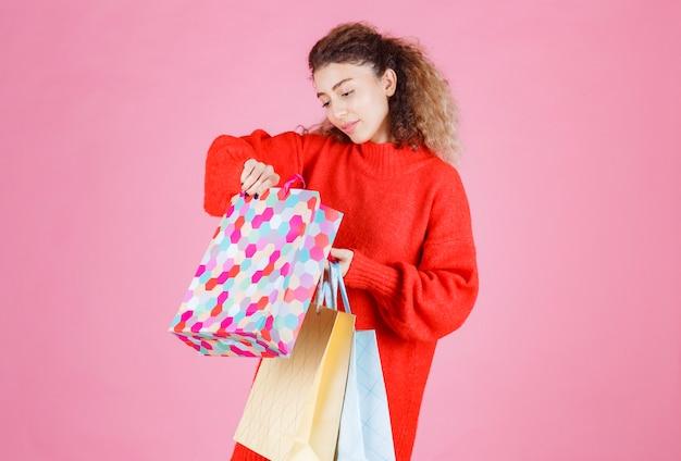 Женщина открывает свои красочные хозяйственные сумки и проверяет продукты.