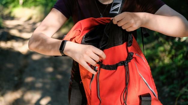 森の中で彼女のオレンジ色のハイキングのバックパックを開く女性
