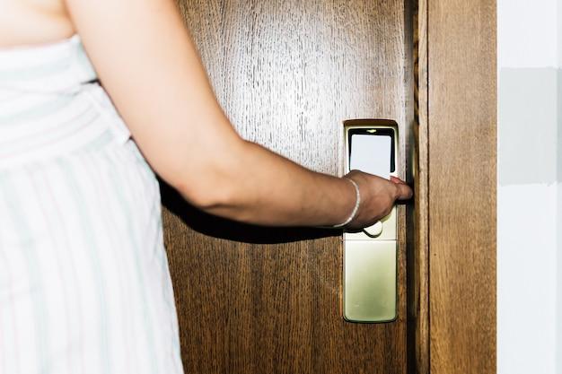 Женщина открывает дверь гостиничного номера с картой