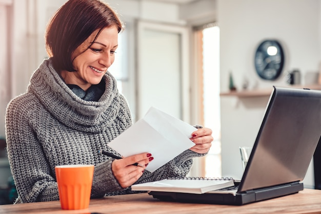 Woman opening letter in the office